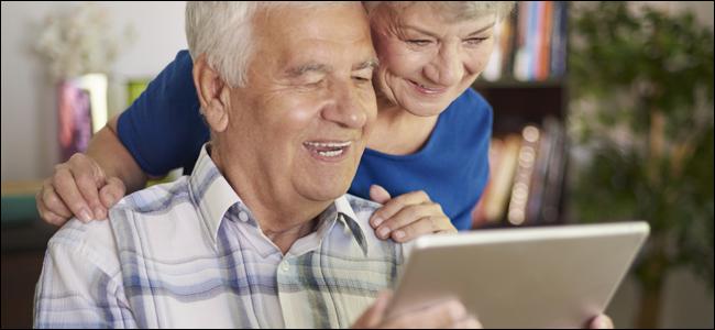 Starsza para uśmiecha się podczas gry z tabletem