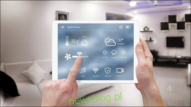 Ręce korzystające z automatyki inteligentnego domu na iPadzie.