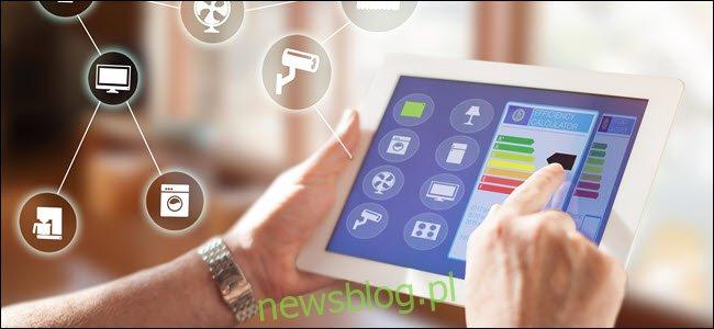 Ręce mężczyzny używające tabletu do sterowania urządzeniami smarthome w aplikacji.
