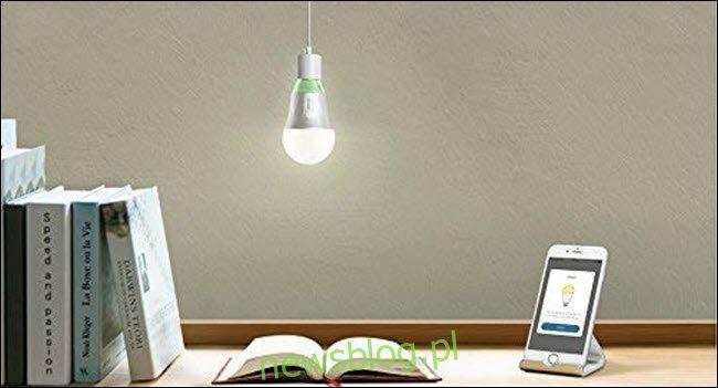 Żarówka TP-Link Wi-Fi zawieszona nad otwartą książką i telefon komórkowy na biurku.