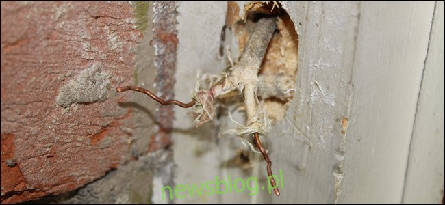Dwa odsłonięte przewody wystające ze ściany.