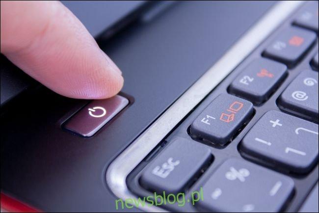 Palec naciskając przycisk zasilania na laptopie PC