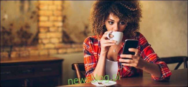 Kobieta siedząca przy stole patrząc na smartfon i pijąc kawę.