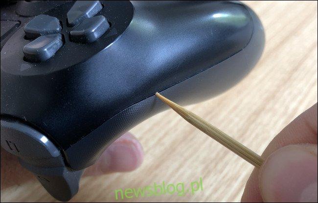 Ręczne czyszczenie szczeliny z boku DualShock 4 wykałaczką.